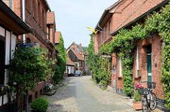 Schmale Gasse mit Kopfsteinpflaster, die Hausfassaden sind mit grünen Kletterpflanzen bewachsen.