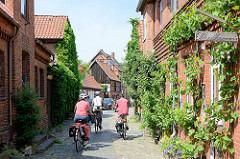 Schmale Gasse mit Kopfsteinpflaster, die Hausfassaden sind mit grünen Kletterpflanzen bewachsen, Radfahrer auf der Tour durch die Stadt.