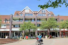 Sonniger Platz mit Geschäften und Wohnhäusern an den Straßen die Ehenknick uund alte Elbgaustraße in Hamburg Eidelstedt.