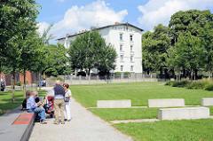Grünanlage mit Sitzbänken / Ruheplätzen auf der Harburger Schlossinsel - im Hintergrund das Harburger Schloss, das als Wohngebäude genutzt wird.