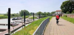 Hafenpromenade mit Radfahrern in Hitzacker; einige Sportboote liegen am Steg der Marina.