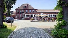 Hotel Hafen in Hitzacker am Kranplatz; Außengastronomie mit Tischen in der Sonne/Sonnenschirmen - beliebte Station, Pause bei einer Fahrradtour eine Elbe.