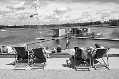 Seepromenade im Norderstedter Stadtpark; Liegestühle in der Sonne - Blick auf den See mit der Wasserskianlage
