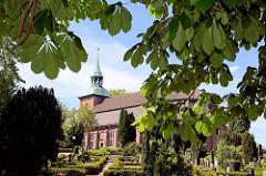 Blick über den Friedhof von Hamburg Ochsenwerder zur Kirche St. Pankratius. Das Schiff der Kirche wurde 1673 bis 1674 errichtet, der Kirchturm 1740.