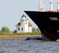 Bug eines Frachtschiffs auf der Elbe - an Land der 1896 gebaute Leuchtturm Julesand in der Sonne.