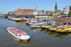 Barkasse und Arbeitsboote liegen im Hamburger Binnenhafen / Hafenbecken in Hamburg-Altstadt; ein Fahrgastschiff bei einer Fleetrundfahrt.
