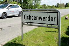Stadtteilschild für Hamburg Ochsenwerder; weiße Schild mit schwarzer Schrift.
