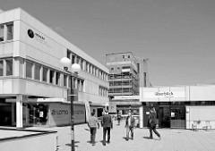 Shopping am Überseering in der Hamburger City Nord - Fussgänger zwischen Betonklötzen, im Hintergrund das Gebäude der Postbank.