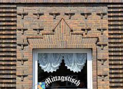 Backsteinarchitektur mit Dekorelementen - Fenster eines Restaurants mit Gardinen, Mittagstisch.