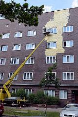 Umstrittenes Kunstprojekt an einer Hauswand eines Wohngebäudes an der Veddeler Brückenstraße im Hamburger Stadtteil Veddel. 300 m² der Fassade wird von einem Hubwagen aus mit Blattgold belegt,