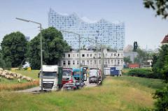 Lastwagenverkehr und eine Schafherde  am Reiherstieg Hauptdeich iin Hamburg Wilhelmsburg; im Hintergrund ein altes Wohnhaus Reiherstiegdeich und das imposante Gebäude der Elbphilharmonie in der Hamburger Hafencity.
