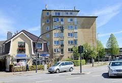 Alt + Neu an der Pinneberger Chaussee iin Hamburg Eidelstedt; Hochhaus mit gelber Ziegelfassade, historisches Einzelhaus mit Geschäften.