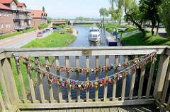 Holzbrücke über die Jeetzel in Hitzacker; Kette mit Liebesschlössern am Geländer - im Hintergrund liegt ein Fahrgastschiff mit Touristen an Bord ab.