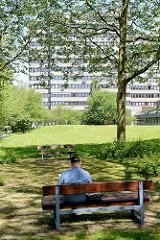 Ruhezone im Grünen - Mittagspause auf der Parkbank - im Hintergrund Hochhaus in der Zentralen Zone.