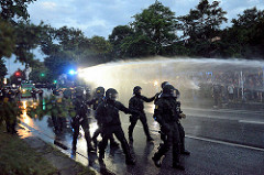 Polizisten in Kampfausrüstung rücken im Schutz eines Wasserwerfers im Schanzenviertel gegen den Protest vor - am Straßenrand freundliche Zuschauer*Innen.