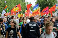 Demonstrationszug am 08. Juli gegen G20 in Hamburg - rote und bunte Fahnen.