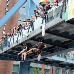 Demonstration am 08. Juli gegen G20 in Hamburg - zwei Demonstrant*innen seilen sich von einer Fussgänger-Brücke über der Willy Brandt Strasse ab - Fotografen.