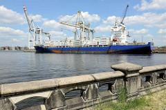 Historische Stein-Brüstung am Hansahöft - Blick über den Hamburger Hansahafen zu einem Frachtschiff am O'Swaldkai.