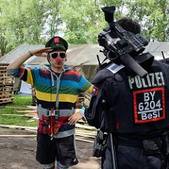 Umstrittenes G20 Protestcamp auf Entenwerder in Hamburg Rothenburgsort - ein politischer Clown mit roter Nase begrüßt einen Polizisten.