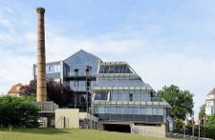 Moderne Glasarchitektur einer Sparkasse in Riesa - alter Fabrikschornstein mit Storchennest.