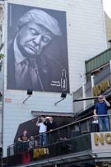 Schlafender Trump - mensch wach auf; Werbung für Cola an der Hamburger Reeperbahn während der Proteste gegen G20.
