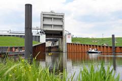 Das Schleusentor der Ernst August Schleuse in Hamburg Wilhelmsburg ist hochgefahren; ein Sportboot fährt ein, um sich in den Spreehafen schleusen zu lassen.