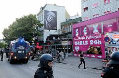 Polizeikräfte mit Wasserwerfer und Sexshop auf der Hamburger Reeperbahn während der Proteste gegen G20 - Trump schläft trotzdem an der Hauswand.