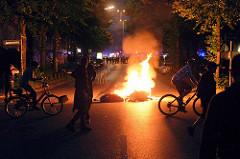 Brennende Müllsäcke beim Protest gegen den G20 Gipfel in Hamburg; im Hintergrund nähern sich vorsichtige Polizisten.