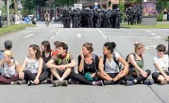 Demonstration Bildungsstreik  - Jugend Gegen G20 in Hamburg; TeilehmerInnen sitzen in der Sonne am Millerntor - im Hintergrund wartende Polzisten in Kampfmontur.