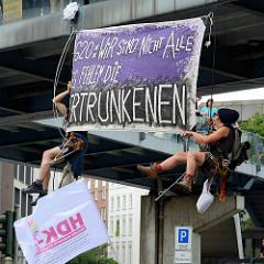 Zwei Demonstrant*innen haben sich von einer Fussgängerbrücke abgeseilt und ein Transpartent aufgehängt: G20: Wir sind nicht alle, es fehlen die ERTRUNKENEN.