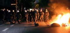 Brennende Müllsäcke, Polizisten sichert die Altonaer Straße bei den Protesten gegen den G20 Gipfel in Hamburg.