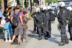 Colour the Red Zone - Protest gegen den G 20 Gipfel in Hamburg, Demonstanten in Sommerkleidung diskutieren mit Polizisten mit Helm und Kampfmontur.
