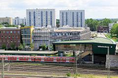 Blick auf den Bahnhof von Hamburg Wilhelmsburg, ein S-Bahn Zug fährt ein; dahinter Einkaufszentrum und Hochhäuser.