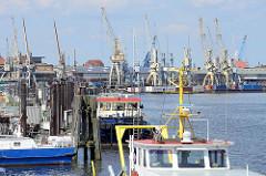 Bilder aus dem Hamburger Hafenbezirk Kleiner Grasbrook - Blick in den Hansahafen, Arbeitsschiffe - im Hintergrund die historischen Kräne vom Hafenmuseum..