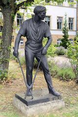 Metallskulptur / Plastik eines Stahlarbeiters vor dem ehem. Verwaltungsgebäude des Stahl- und Walzwerkes Riesa - jetzt Amtsgericht.