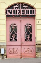 Historische Eingangstür mit schmiedeeisernem Rankwerk als Glasschutz - Schriftzug Weinhold; Architektur in Riesa / Elbe.