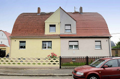 Doppelhäuser mit unterschiedlicher Fassaden- Dachgestaltung; Spitztonnendach / Zollingerdach; Architektur in Riesa.