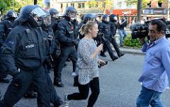 Eine Fernsehmoderatorin  wird von einem Schwarzen Block von der Straße gejagt - Protest gegen den G20 Gipfel in Hamburg.