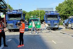 Wasserwerfer + Räumpanzer sperren die Strassen am Millerntor wg.  dem Protest gegen den G20 Gipfel in Hamburg. Fernsehteam + FahrradfahrerIn.