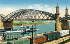 Altes Bild der Brücke über die Elbe bei Riesa; im Vordergrund Eisenbahnwaggons am Kai / Abdeckplane mit der Aufschrift Schott + Genossen, Glaswerk Jena. Ein Dampfschiff / Raddampfer, Ausflugsschiff Bodenbach fährt auf der Elbe flussaufwärts.