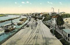 Historische Ansicht vom Hafen in Riesa; Güterwaggons auf den Gleisen - ein Schleppzug mit mehreren Elbkähnen fährt elbaufwärts