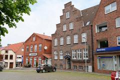 Architektur am Markt von Wilster; expressionistisches Backsteingebäude mit Treppengiebel, erbaut 1927; lks. das Wilster Kulturhaus.