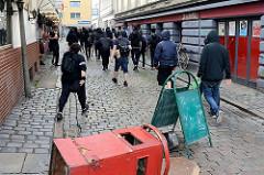 Der sogen. Schwarze Block beim Protest gegen den G 20 Gipfel in Hamburg; im Vordergrund ist eine Barikade errichtet - biertrinkende Keipenbesucher unbehelligt  sehen zu.