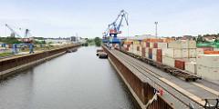 Containerlager und Portalkräne mit Güterwagen am Hafen in Riesa.