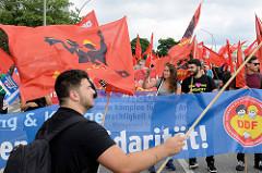 Demonstrationszug am 08. Juli gegen G20 in Hamburg; rote Fahnen.