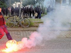 Demonstration Welcome to Hell - ein kleiner Müllsack brennt qualmend, Schwarzer Block beim Protest gegen den G20 Gipfel in Hamburg.