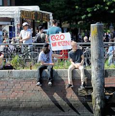 Veranstaltung Welcome to Hell auf dem Fischmarkt - Protest gegen G20 in Hamburg; Plakat auf der Kaimauer am Fischmarkt G20 MA' KOTZEN: