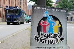 Plakat in der Hafencity - Runter vom Sofa! Auf die Straße - Hamburg zeigt Haltung beim G20-Gipfel am 8. Juli 2017; im Hintergrund Wasserwerfer.