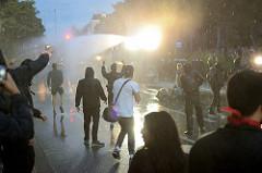 Demonstration Welcome to Hell gegen den G20 Gipfel in Hamburg - Wasserwerfer beleuchten die Kreuzung am Pferdemarkt im Schanzenviertel, Demonstranten blockieren die Keuzung und warten auf die Dusche.