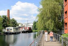 Fussweg über dem Wasser des Veringkanals in Hamburg Wilhelmsburg - im Hintergrund Hausboote, Arbeitsboot bei der Honigfabrik.